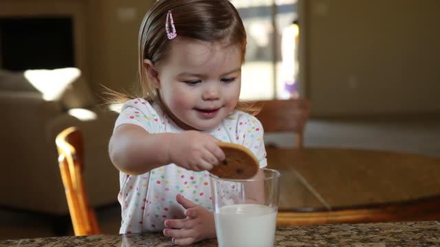 Little girl having milk and cookies video