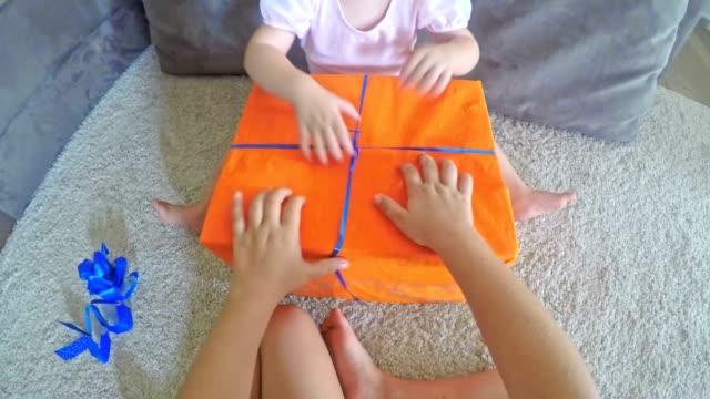 POV Little girl helping her older sister open a gift video