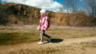 Little girl hiker in a pink jacket with a backpack walks in the canyon video