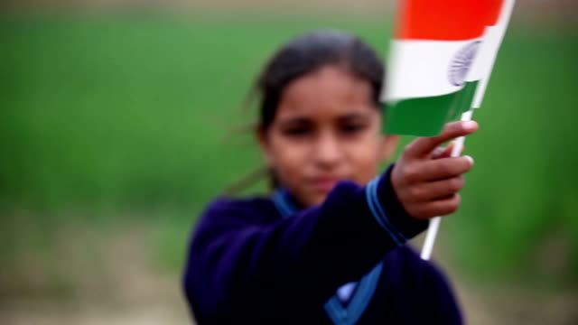 Little girl holding Indian national flag in the nature video