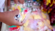 Little girl holds colorful sweet candy in the store video