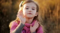 little girl in a sunset light blows a kiss to the camera video