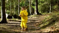 Little girl in a yellow rubber suit is jumping in a puddle.  Slow Motion video