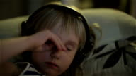 A little girl in headphones rubbing her eyes and yawning. video