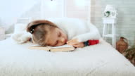 Little girl in pajamas, fell asleep while reading a book, covered with white woolen blanket. video