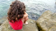 Little girl in red summer dress sitting on the rocks on the sea shore video