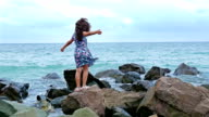 Little girl in red summer dress standing on the rocks on the sea shore and looking to the sea video
