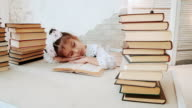 Little girl in school uniform, fell asleep while reading a book. video