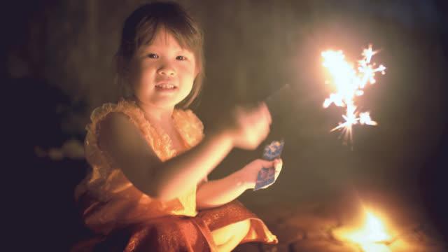 Little girl in thai dress with a sparkler in loi kratong festival video