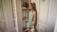 A little girl in the dress looks thoughtfully standing the bright room video
