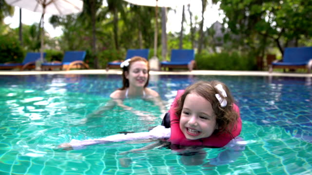 Little girl in the swimming vest floating in the pool with his mother. video