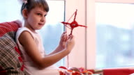 Little girl in white shows his crafts. video