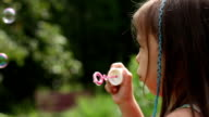 Little girl is blowing a soap bubbles outdoors video