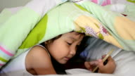 Little girl is playing game on the phone under the covers. video