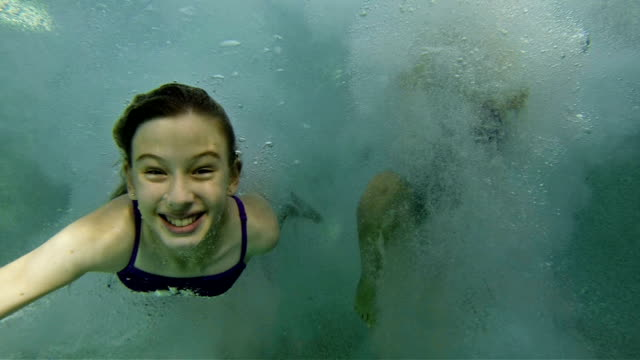 Little girl jumping & swimming in Pool video