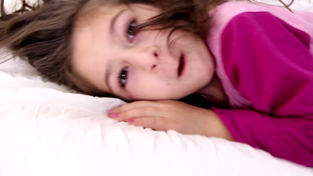 Little girl jumps on a pillow and closes eyes video
