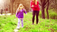 Little girl learning to walk in park with mother video