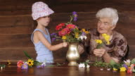 CU PAN Little Girl Learns From Her Grandmother How To Arrange Flowers In A Vase. Real People, Rural Scene. video