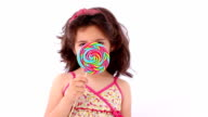 Little girl licking a lollipop, close up video