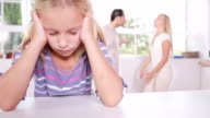 Little girl looking depressed in front of fighting parents video