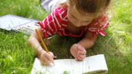 Little girl lying on grass and drawing video