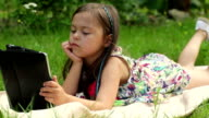 Little girl lying on grass and playing tablet pc video