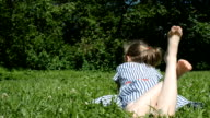 Little girl lying on green grass in the park. video