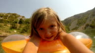 Little girl making funny faces while lying on air mattress video