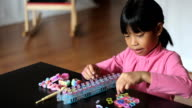 Little Girl Making Rainbow Bracelet On Her Loom video