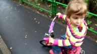 Little girl on bicycle talking and then riding from camera video