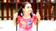 Little girl on swing smiling at camera video