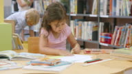 DS Little girl painting a drawing in library video