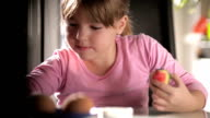 Little girl painting Easter eggs at home video