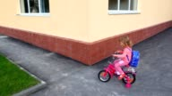 Little girl pedaling on bicycle in foreyard near apartment building video