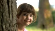 Little girl peeking from Behind Tree video
