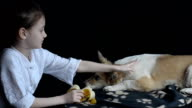 Little girl petting the dog and feeding the banana video