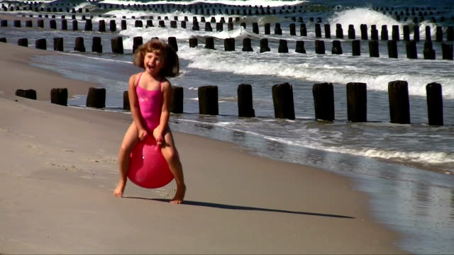 Little girl playing at the beach video