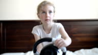 Little girl playing game with steering wheel. video