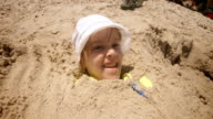 Little Girl Playing In The Sand Buried up to her Head video