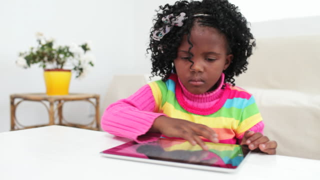 little girl playing on digital tablet video