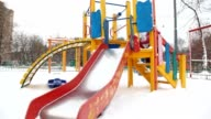 Little girl playing on slide in deep snow city playground video