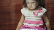 Little girl playing with a digital tablet video