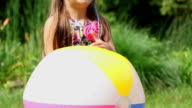 Little girl playing with ball outdoors, slow motion video