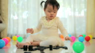 Little girl playing with black domino video