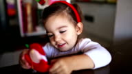 Little girl playing with christmas ornaments video