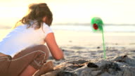 Little girl playing with green toy windmill video