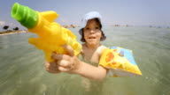 Little Girl Playing with Squirt Gun and Spraying Water at Camera video