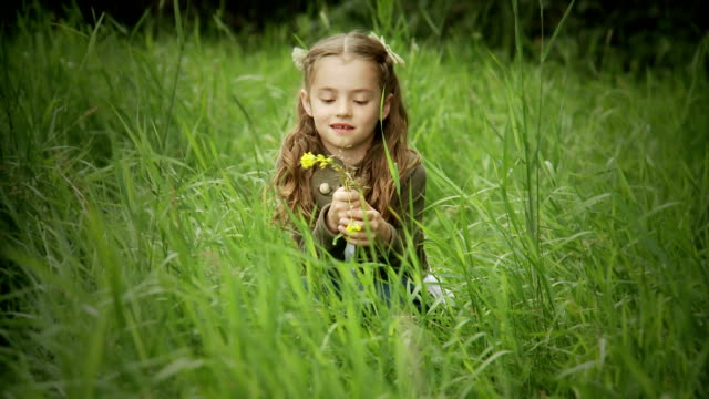Little girl plays in the grass. video