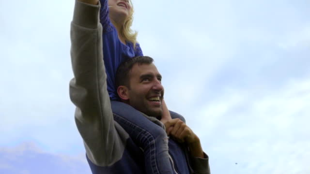 Little girl plays superman on dads shoulders video