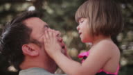A little girl plays with her father's face as he holds her up video